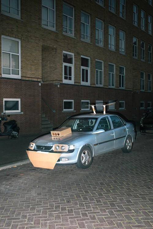 carro en una calle de Amsterdam con unas piezas hechas de cartón pegadas con cinta adhesiva