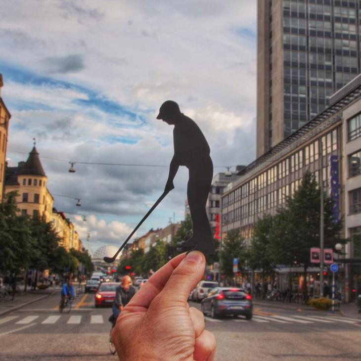 Recorte de papel en figura de un golfista simulando que el Arena Globen, Estocolmo es una pelota de golf