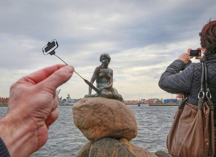 estatua de la sirenita en Copenhague, con un recorte de papel en su mano