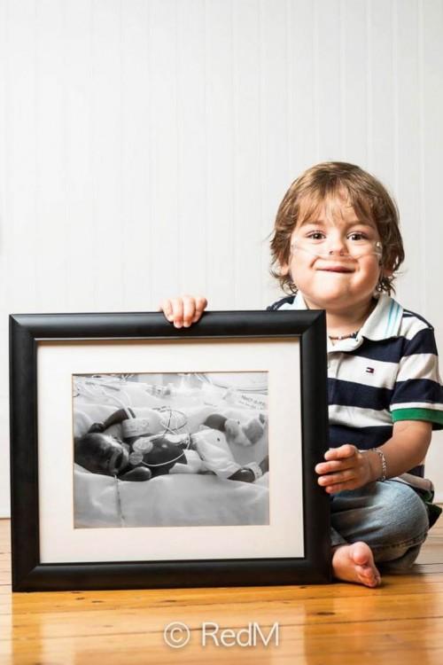 Niño sentado en el suelo sosteniendo un retrato a un costado de él