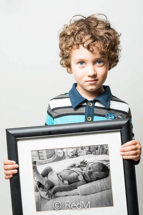 niño poniendo un retrato frente a él cuando fue un bebé prematuro