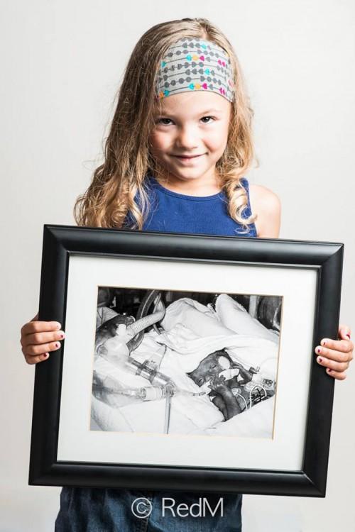 niña con un retrato frente a ella de cuando era una bebé