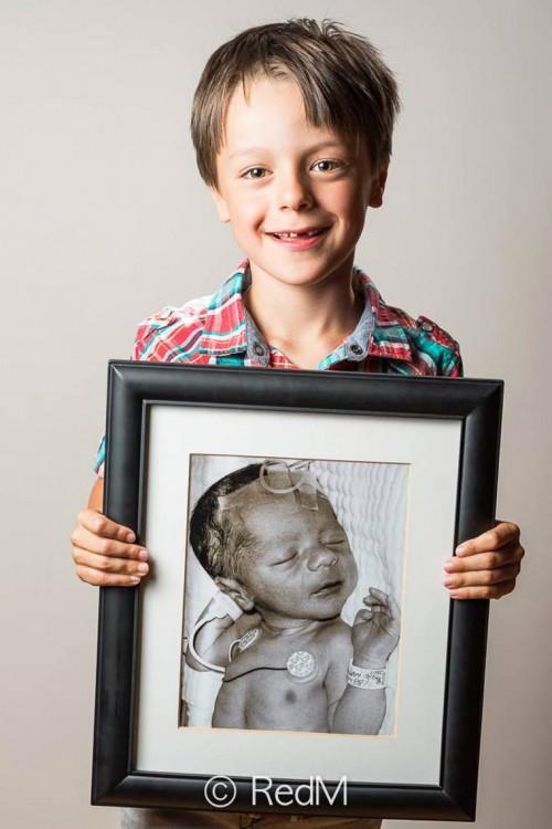 Foto de un niño agarrando un retrato de él cuando era bebé