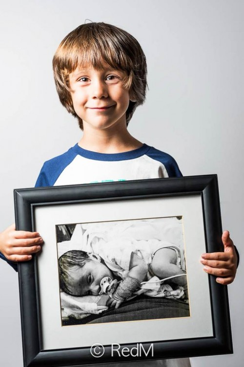 Niño sonriendo y mostrando su retrato de cuando era bebé
