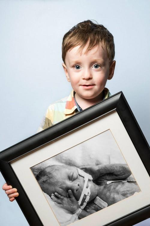Fotografía de un niño sosteniendo un retrato de él cuando era bebé