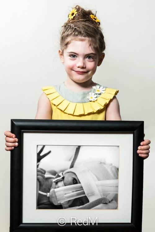 Margot niña cargando un retrato frente a ella