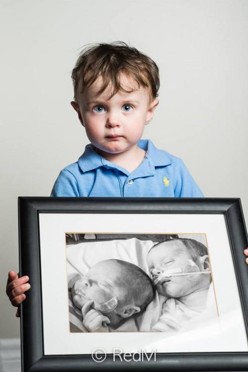 Niño cargando un retrato de él y su hermana gemela cuando eran bebés
