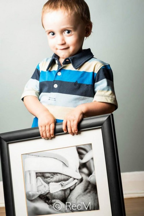 Niño parado sosteniendo un retrato en sus manos