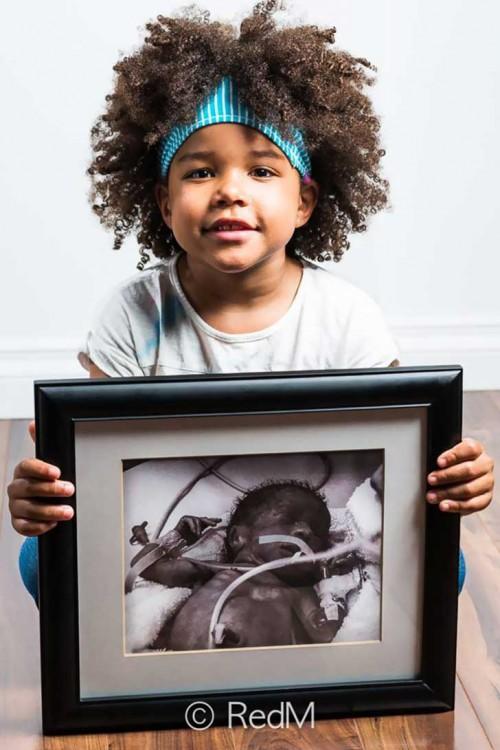 Niña de cabello chino sentada en el suelo sosteniendo un retrato en sus manos