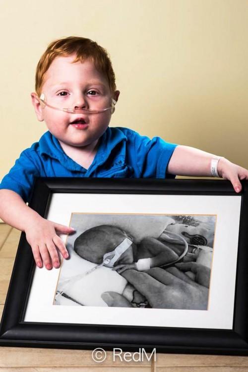 Niño pelirojo sentado en el suelo agarrando con sus manos un retrato de él cuando era un bebé