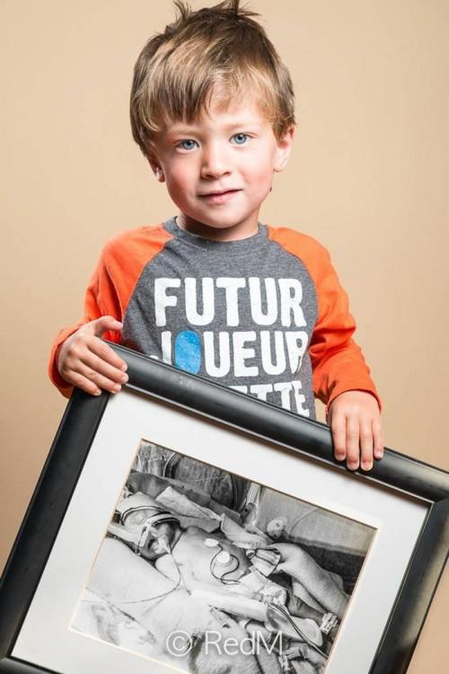 niño con un retrato de él cuando era bebé