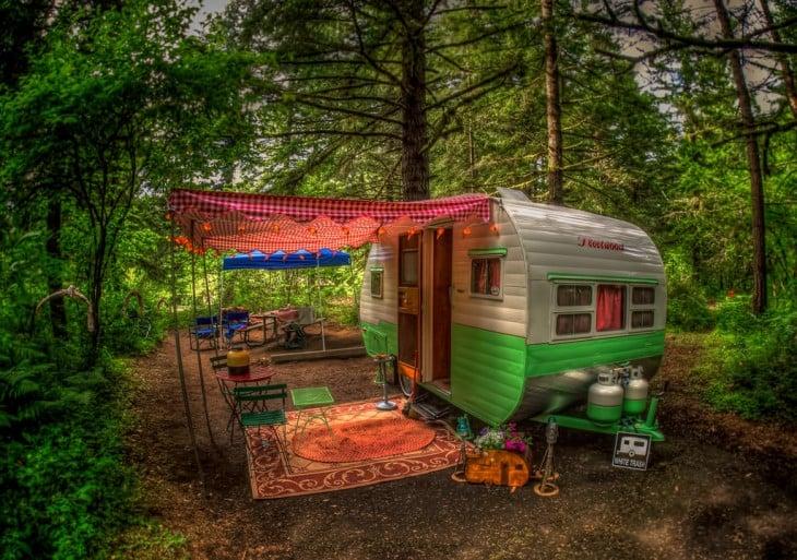 remolque cerca de un bosque con una alfombra en su exterior