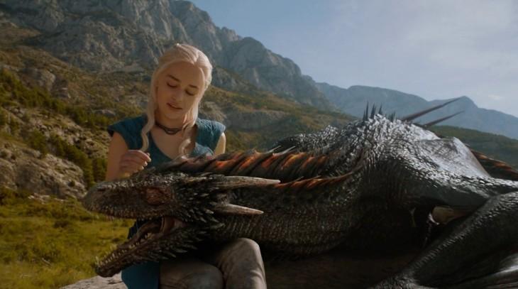 Daenerys Targaryen acariciando la cabeza de un dragón que esta sobre sus piernas