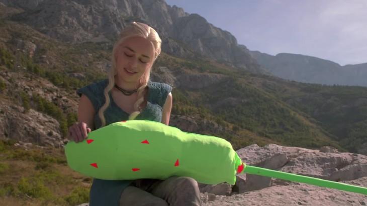actriz que interpreta a Daenerys Targaryen en Game of thrones con un objeto de pantalla verde en su regazo