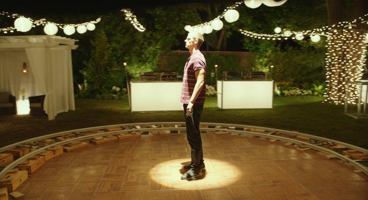 chico parado en medio de un escenario rodeado de luces