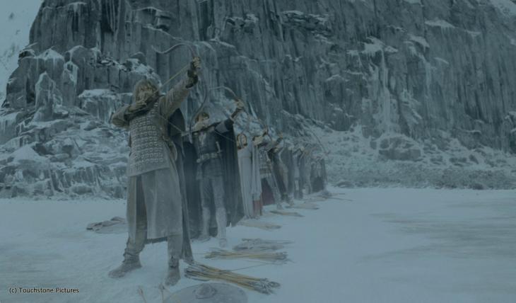 Personajes de la película el rey Arturo apuntando con un arco en una escena de nieve