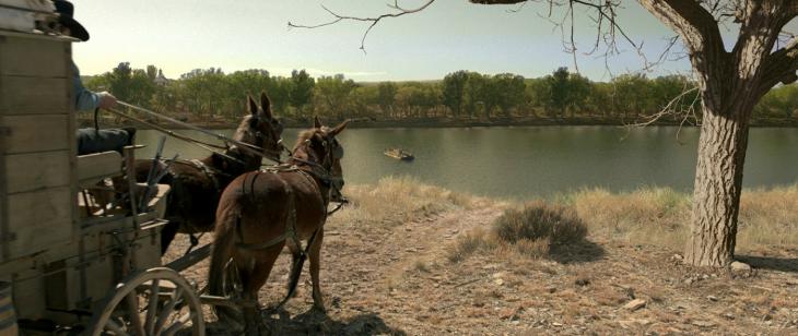 escena de una persona jalando una carreta con dos caballos en la película de The Homesman