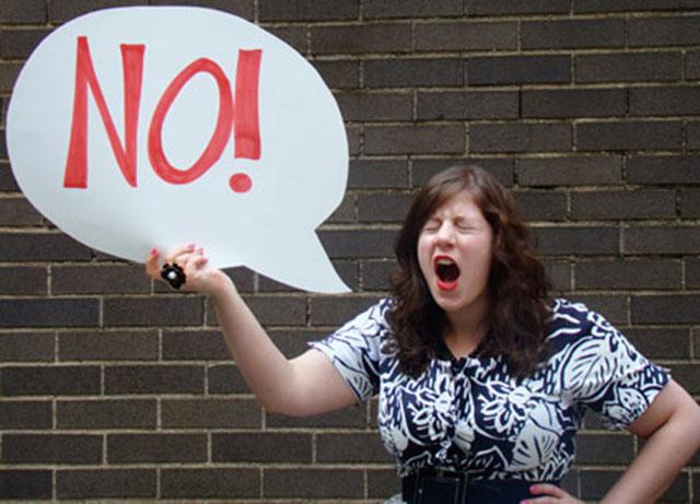 Mujer con un cartel en su mano que dice NO!