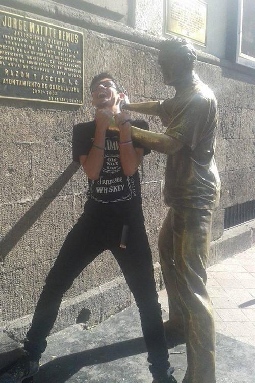 foto de un chico que simula estar siendo estrangulado por una estatua