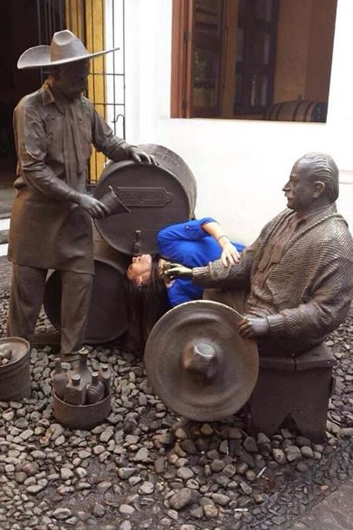 foto de una chica interactuando con unas estatuas simulando que va a tomar cerveza de un barril