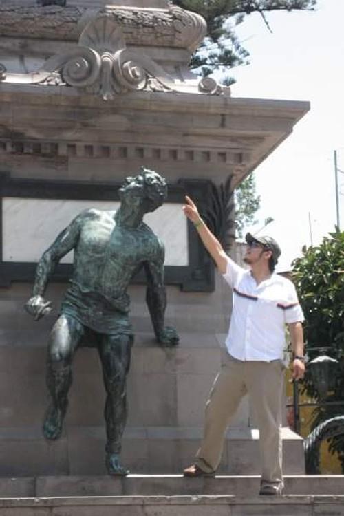 foto de un chico que esta señalando algo a un costado de una estatua que parece estar volteando