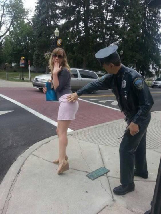 foto de una estatua de policía tocando un glúteo de una chica en medio de la calle