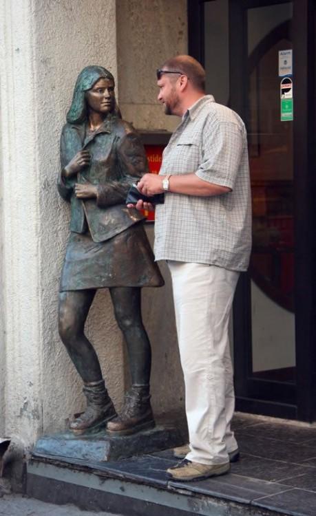 foto de un hombre con la cartera en la mano a un lado de una estatua con figura de chica en minifalda