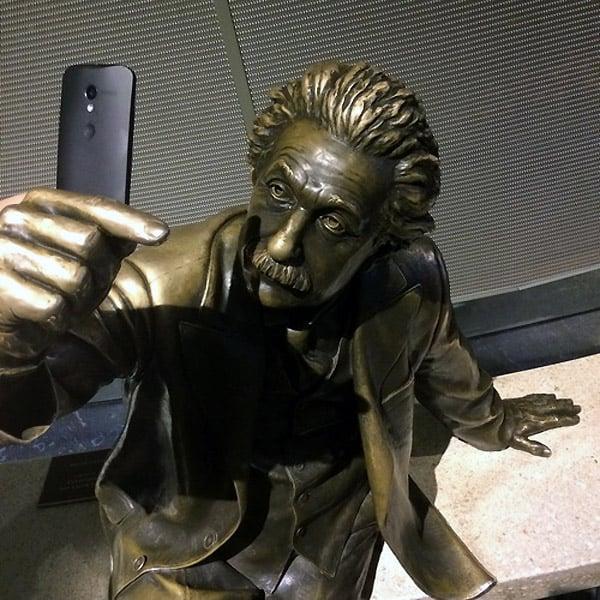 estatua de albert einstein con un celular simulando tomarse una selfie