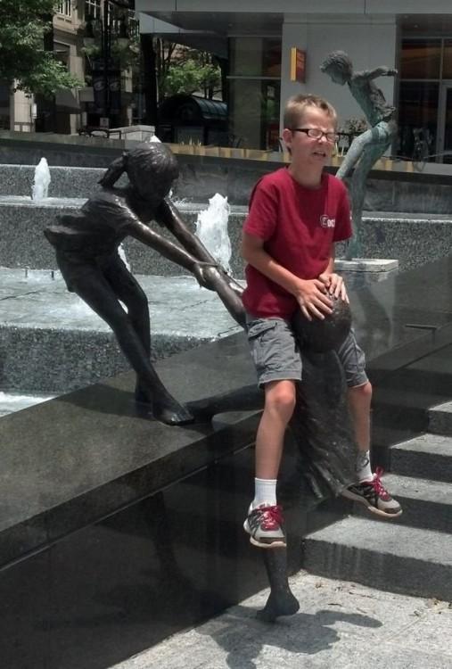 foto de un niño arriba de una estatua con cara de tristeza