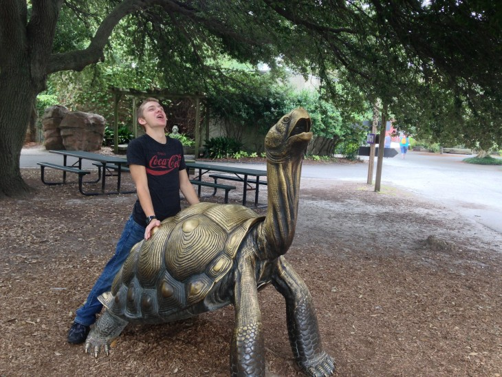foto de un chico sobre una estatua de tortuga simulando su misma pose