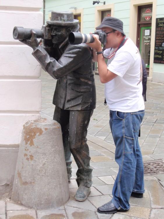 chico a un costado de una estatua que parece estar tomando una fotografía