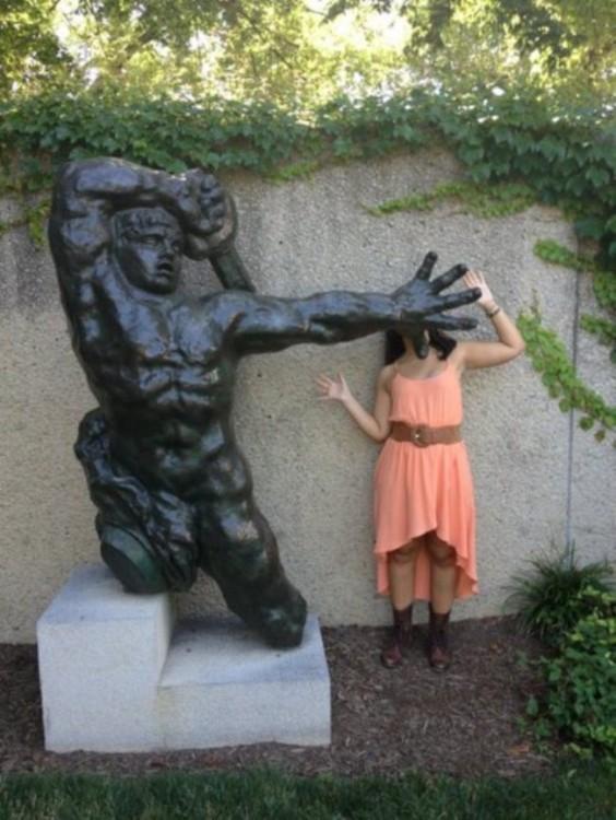foto de una estatua que parece estar estampando a una chica contra la pared