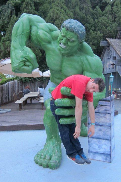 chico arriba de una estatua de hulk que simula estar a punto de golpearlo