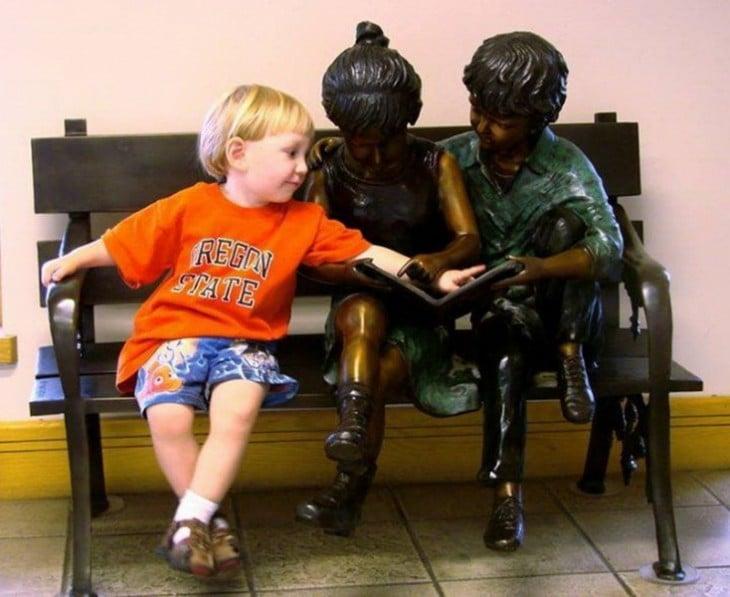 foto de un niño con dos estatuas de niño señalando un libro