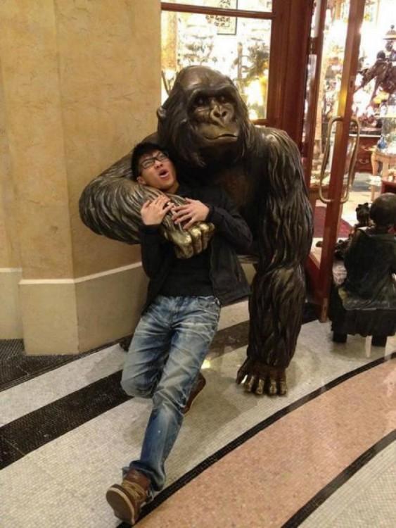 chico simulando que una estatua de gorila lo esta atacando
