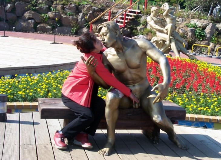 foto de una mujer a un lado de una estatua que parece agarrandole sus genitales