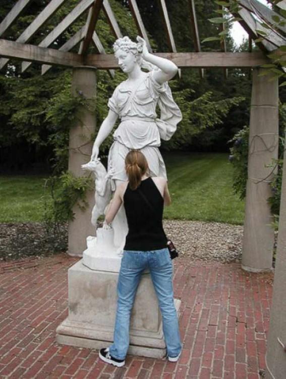 chica con la cara en medio de las piernas de una estatua