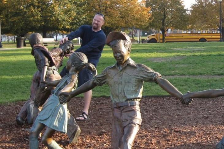 fotografía de una estatua de unos niños jugando a la ronda mientras un hombre simula estar agarrando la cabeza de una estatua