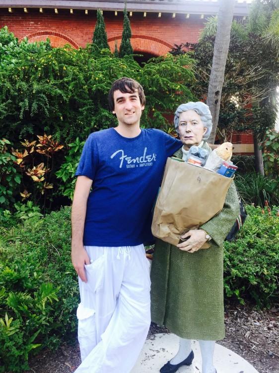 foto de un chico abrazando a una estatua de una anciana con las compras en la mano