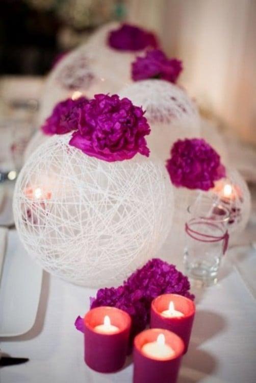 centros de mesa blancos con flores y unas veladoras en la mesa