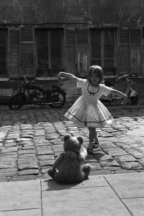 niña bailando frente a su oso de peluche