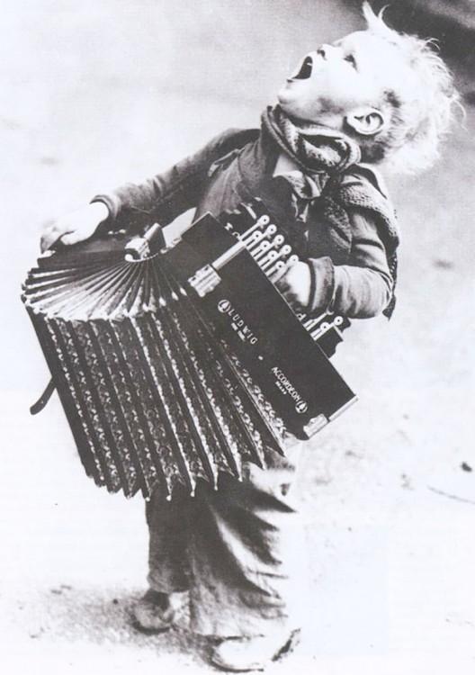 niño cantando y bailando con una acordeon