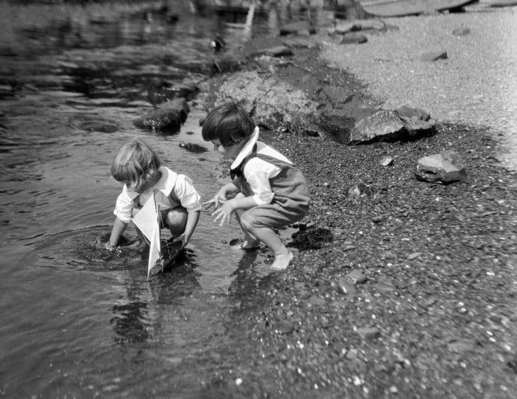 niños jugando a los barquitos en un charcvo