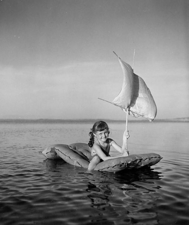 niña con un flotador en el rio o en el mar simulando un barco
