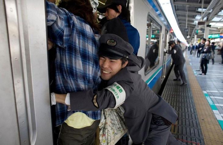 persona intentando acomodar personas dentro de un tren en Tokio, Japón