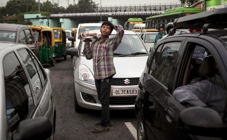Niño vendiendo cocos a la mitad de la calle en Nueva Delhi, India.
