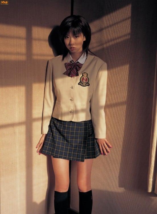 chica con uniforme de colegiala en la esquina de un cuarto