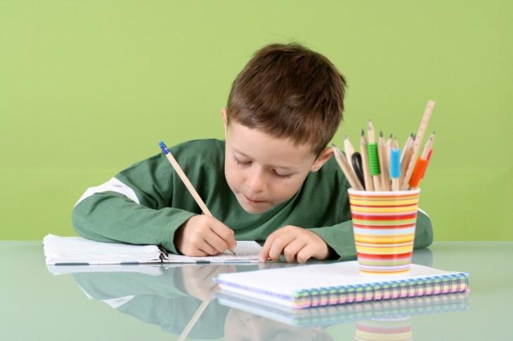 Niño escribiendo con lápiz sobre una hoja de papel