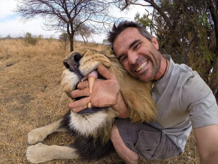 selfie de un hombre junto a un león