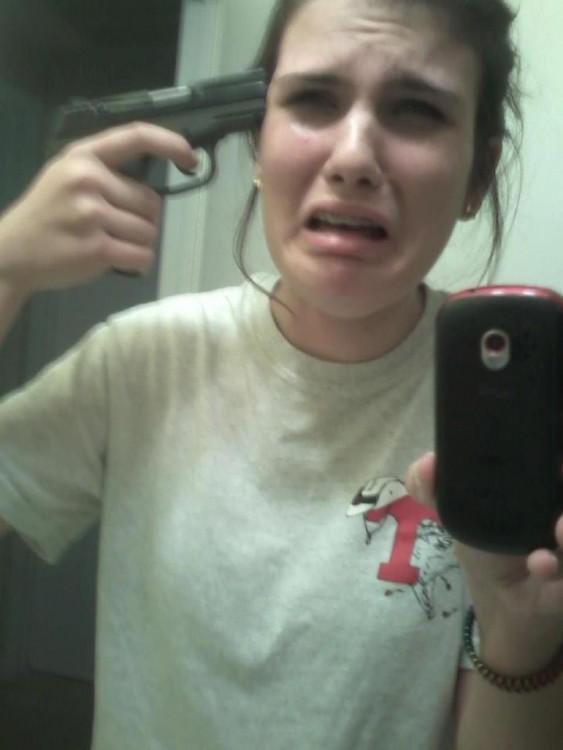 Selfie de una chica con una pistola apuntando a su cabeza